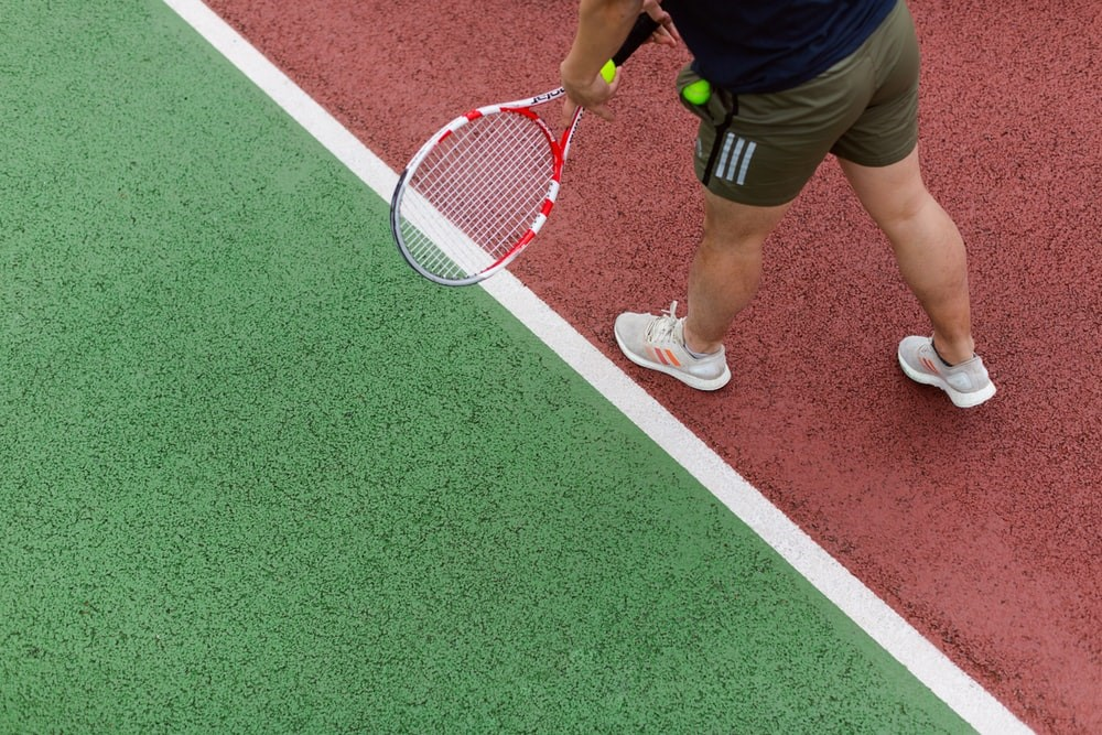 person in black shorts holding red and white tennis racket